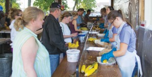 Corn fest volunteers butter corn for festival patrons.
