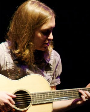 Whitney Mann strumming her guitar at the Broom Street Theater.