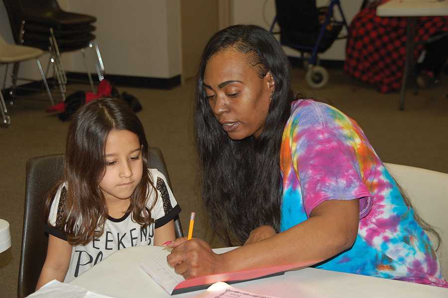 China Miller helps a student at the after school Level Up Homework Club.
