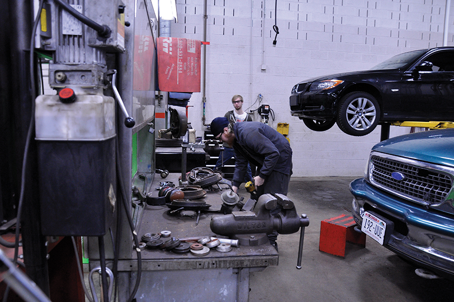 Two Madison College students work on a vehicle's brakes in one of the college's automotive bays during class.