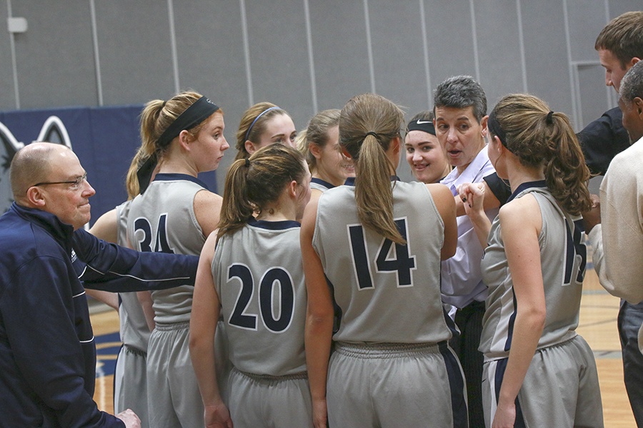 Rachel Slaney joins her Madison College teammates in a huddle during a timeout.