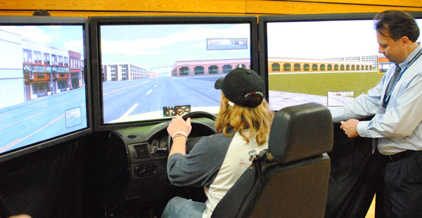 Madison College student Spencer White drives the virtual drunk driving simulator simulator as the operator increases the virtual level of alcohol.