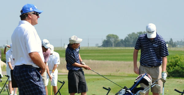 Madison College golf coach Pat Gorman watches two of his players warm up for a recent golf invitational in Janesville.