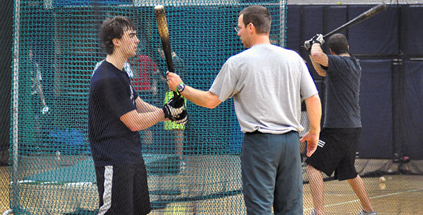 Madison College baseball coach Mike Davenport works with a hitter during a recent practice.