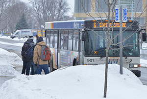 Students stand out in the cold weather as they wait at the bus stop near the Truax campus to board a Madison Metro bus.