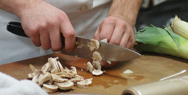 Mushrooms are sliced in the kitchen in preparation for a meal to be served in the gourmet dining room.