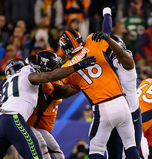 Peyton Manning (18) of the Denver Broncos comes under pressure from the Seattle Seahawks' defense, causing him to throw an interception, in the first half of Super Bowl XLVIII at MetLife Stadium in East Rutherford, N.J., Feb. 2.