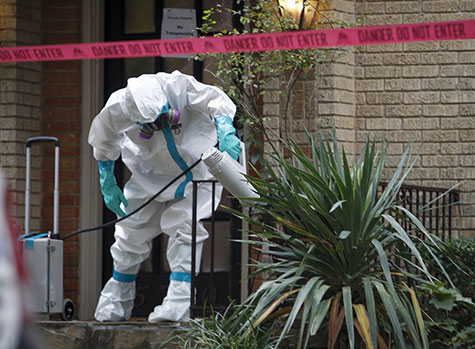 A worker with CG Environmental-Cleaning Guys sprays disinfectant outside the Marquita Street apartment building where a health care worker believed to be infected with Ebola lives on Oct. 12, in Dallas.