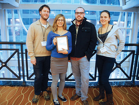 Clarion staff members, from left, Joe Pruski, Natalie Connors, Frederic Hewitt and Onawa Powell, show one of the awards the newspaper won at the Associated Collegiate Press National College Media Convention.