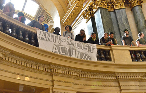 Students hold a banner in the State Capitol rotunda during a protest earlier this month.