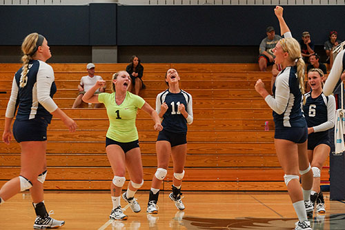 The team celebrates a point during the 2015 Volleyball Alumni match