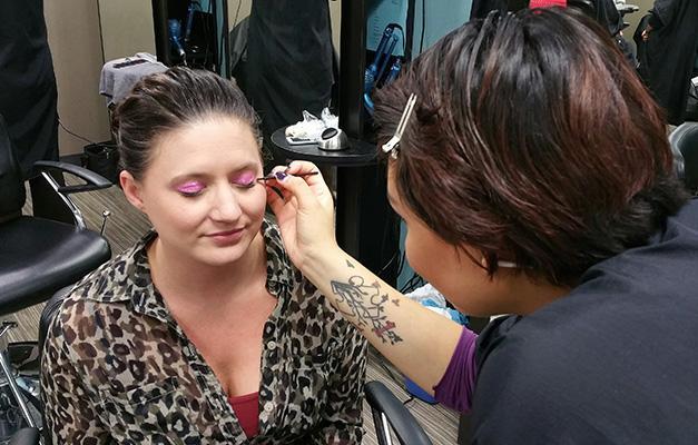 Rebecca Waraczynski getting her eye makeup done by Josaba Yerena Guzmán for breast cancer awareness.