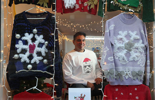 Joseph Dunne sits in the front window of his Christmas Sweater Depot pop-up store selling ugly Christmas sweaters in Chicago.