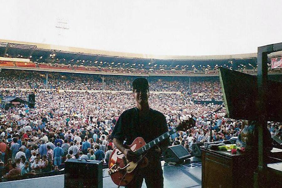 Todd Bowie tunes a guitar on stage before the start of an Eagles concert.