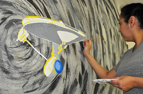 Raquel Manning paints a section of the new mural on the wall of the cafetaria.