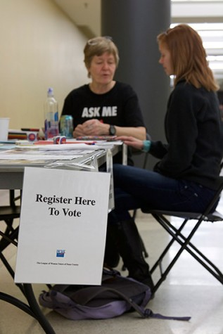 Gil Bliss, a volunteer from the League of Women Voters, helps a student register to vote at the Truax Campus.