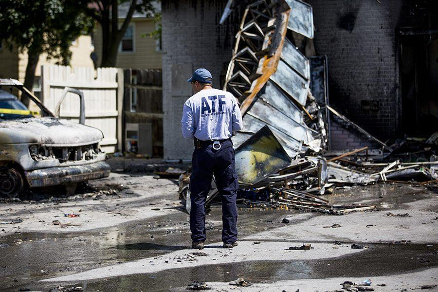 A member of the Bureau of Alcohol, Tobacco, Firearms and Explosives investigates the scene of a gas station on Aug. 14, 2016, that was destroyed during protests the day before in Milwaukee, Wis.