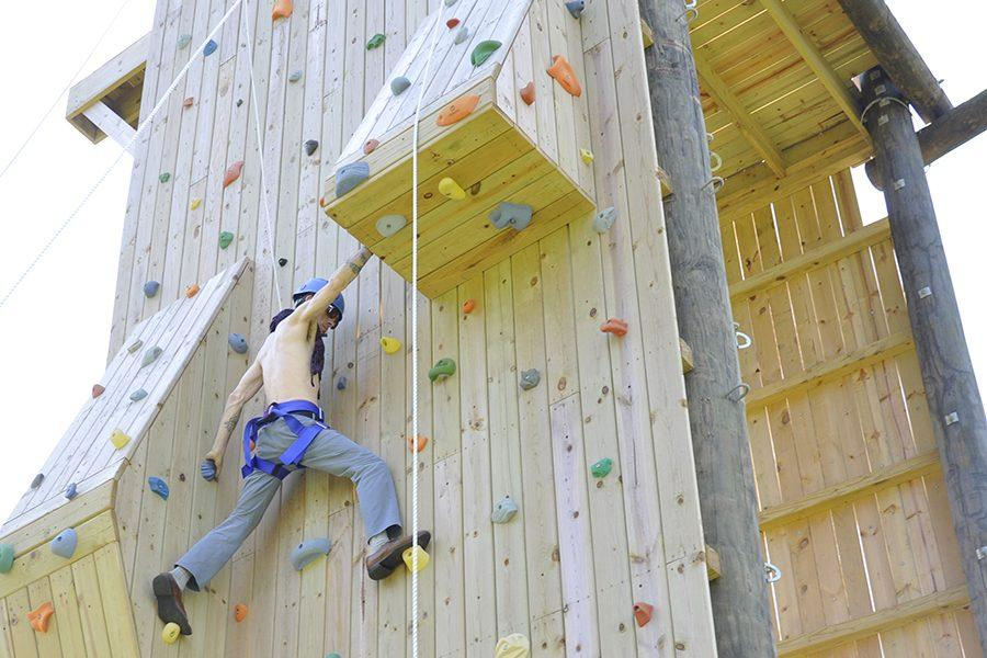 Patrick Kempfer scales the climbing wall with support from other members of the newspaper staff.