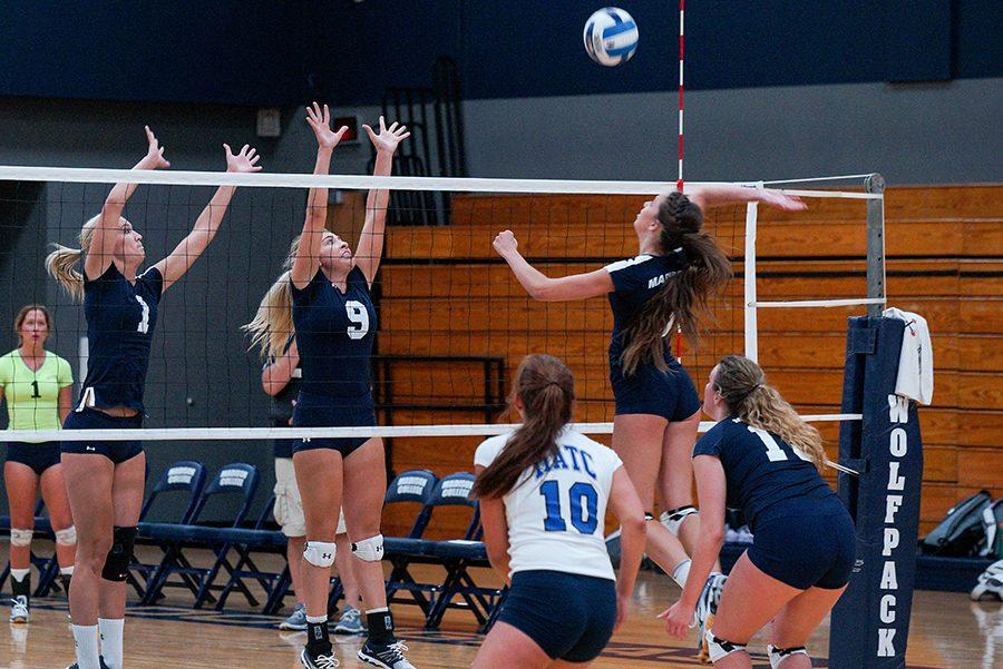 Sophomores Andrea Bauer (right) and Taylor Genthe block during the WolfPack Almuni game on Aug. 12.