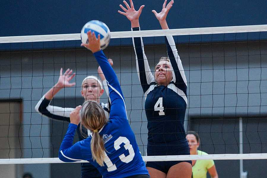 Madison College volleyball player Kiefer Zimmerman (4) leaps to block the ball during a 3-0 win over Elgin Community College on Aug. 25 as TeAnn Harms looks on.