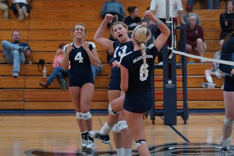 Madison College volleyball players Keifer Zimmerman (4), Natasha Swiggum (13) and Taylor Genthe (6) celebrate a point against Rock Valley College on Sept. 29.
