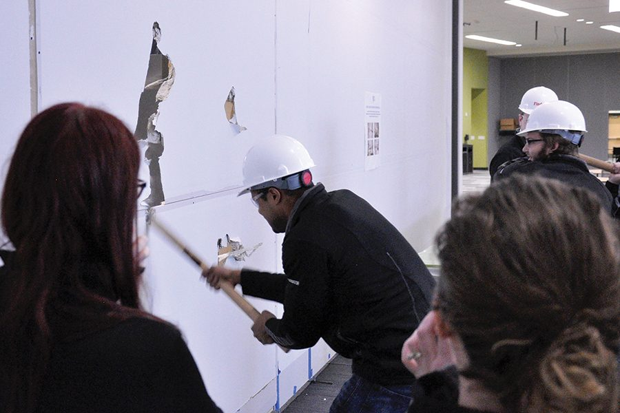 Meshan Adams, a member of the Madison College Student Senate, takes a swing with a sledge hammer at the temporary wall that separated the completed cafeteria seating area from the section that was still under construction during a ceremony on Dec. 21.