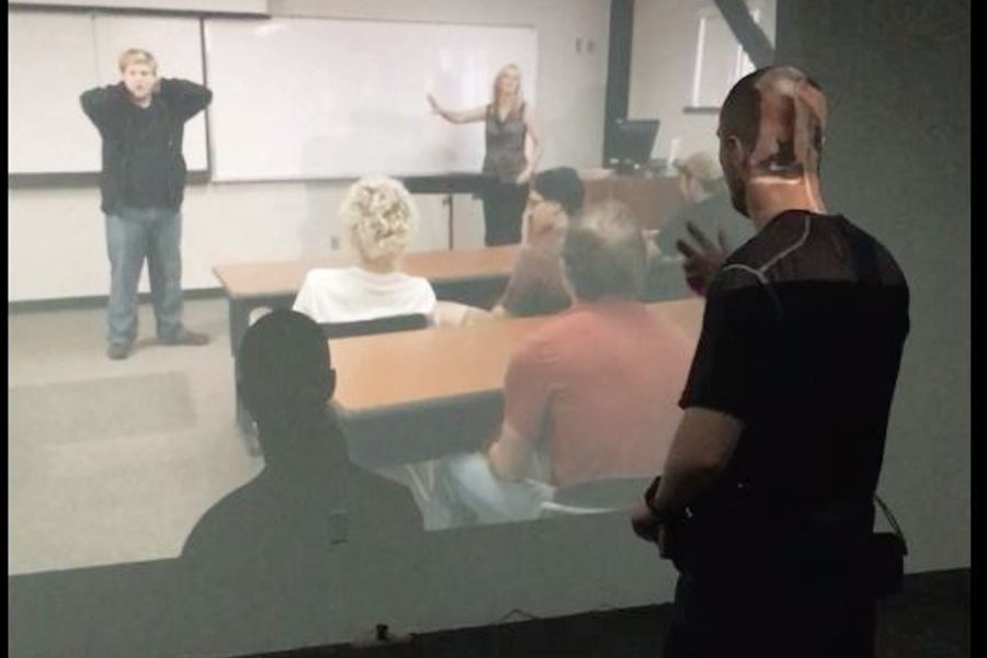 Officer Weckerly participates in a video scenario at the Protective Services building.
