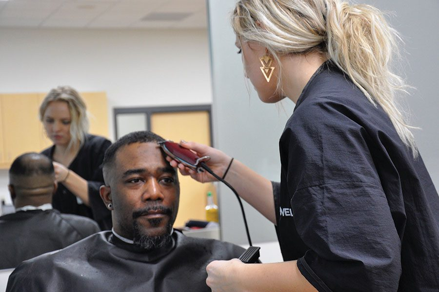 A barber-cosmetology student trims a customer's hair in the new TruStyle Salon at the Madison College Truax campus.