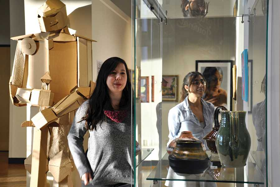 Yahara Journal graphic designer Kristina Karlen, left, and editor Paulina Kababie review the items on display in the student art show in the Truax Gallery.