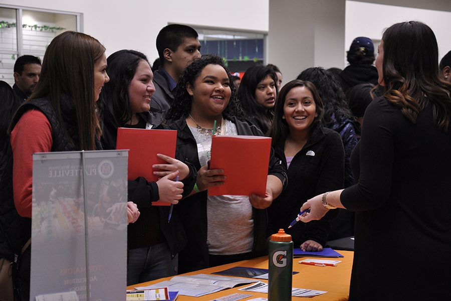 A group of high school students visits an information table during the Latino Youth Career and College Fair on March 17. The Asian Youth Career and College Fair will be held at Truax on April 7.