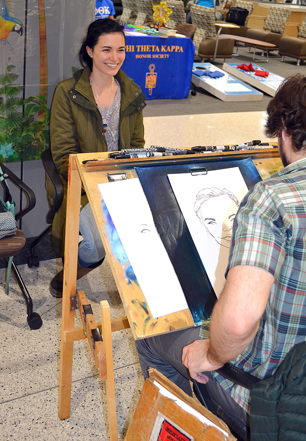Caricature artist Theo Howard draws for a student at the grand opening ceremony.
