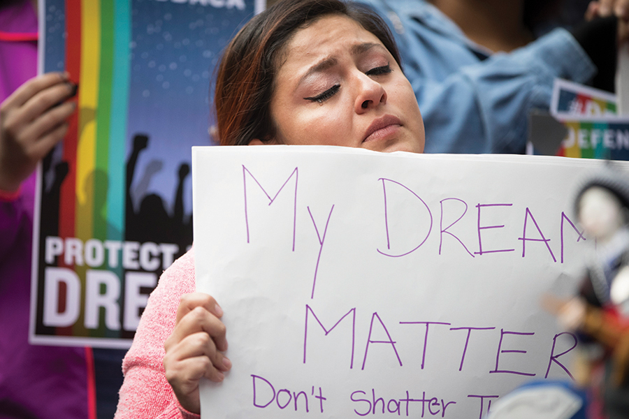 Evelin Hernandez 27 cries as she holds a sign reading