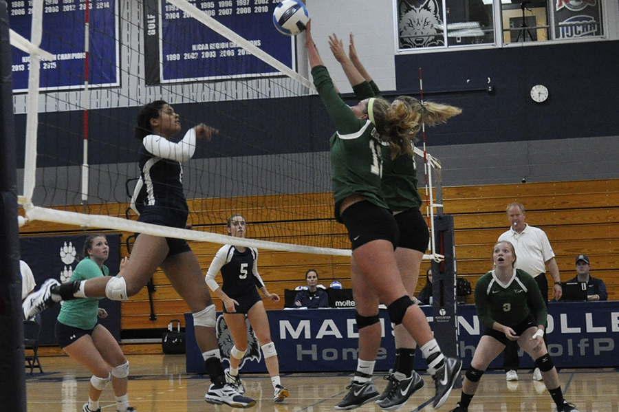 Madison College's Lori Sanders, left, hits the ball through the block of two opponents during a recent match.