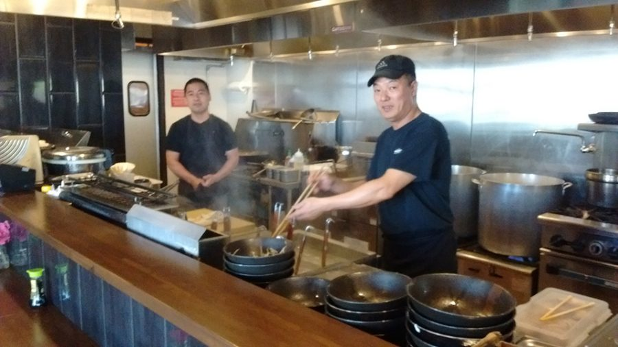 Workers prepare a meal at Ramen Station.