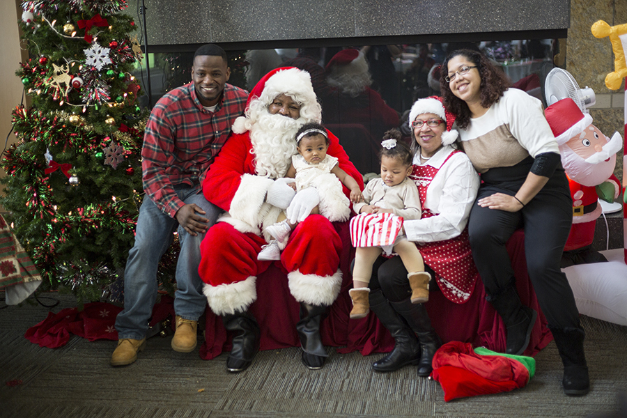 Louis Bentley, left, and his son, Luca Bently, visit with Santa and Mrs. Claus at the Snacks with Santa event in the Truax Campus Gateway on Dec. 2. Louis Bentley is a 2008 graudation of the college's EMT program.