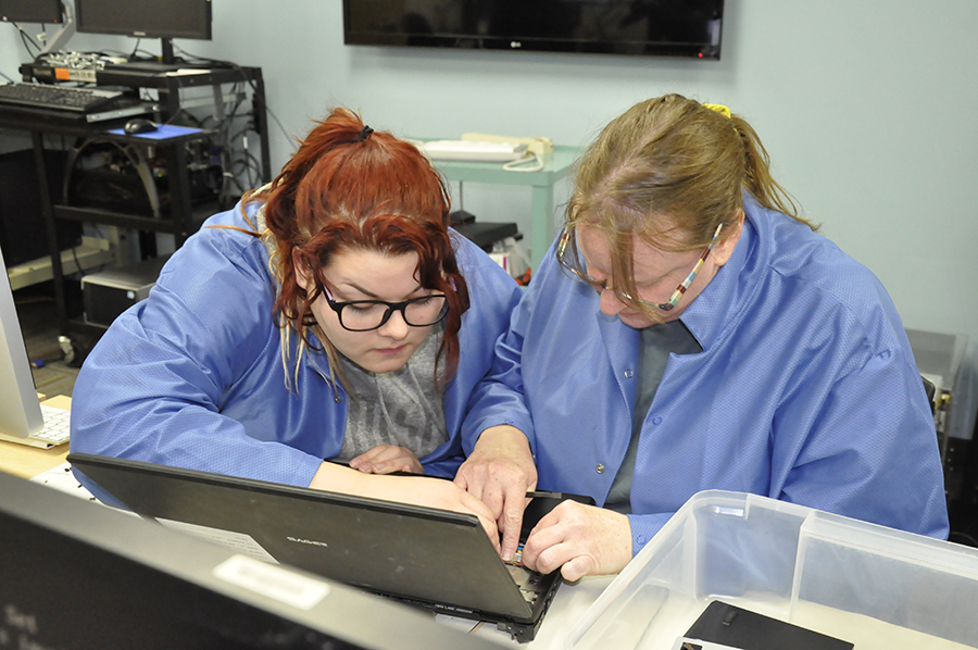 Members of the Madison College WolfPack Techies work to troubleshoot potential computer problems.