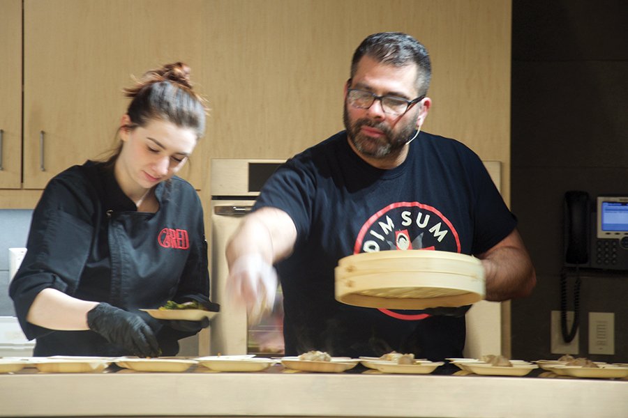 Culinary instructor Joe Gaglio works with a former student to serve dumplings at a recent chef series event.