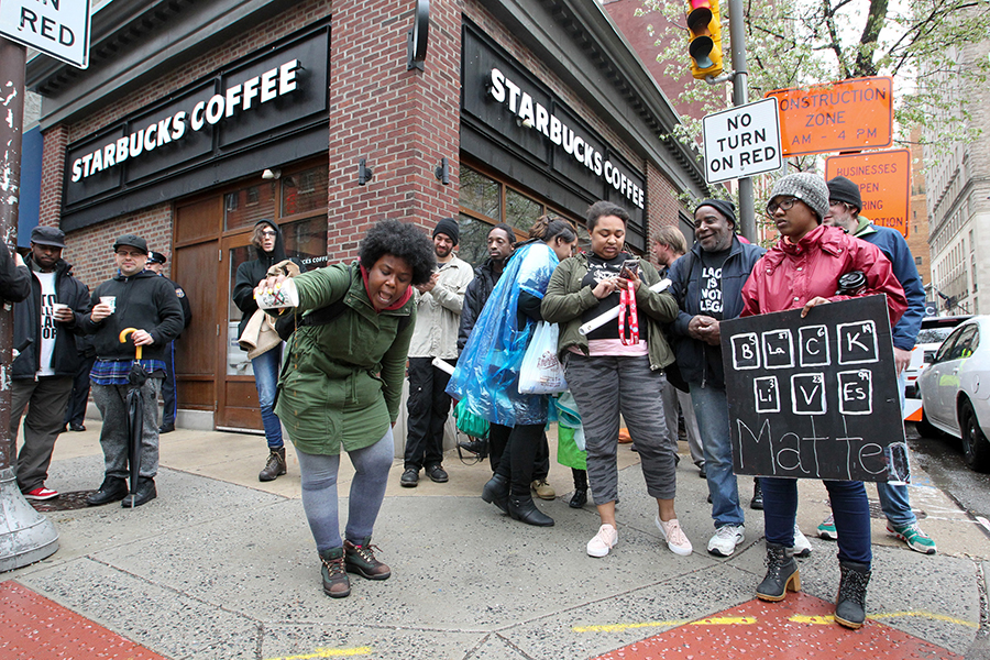 Protestor Aurica Hurst, from West Philadelphia, pours out coffee in front of Starbucks at 18th and Spruce Streets on Monday, April 16, 2018 in Philadelphia, Pa.