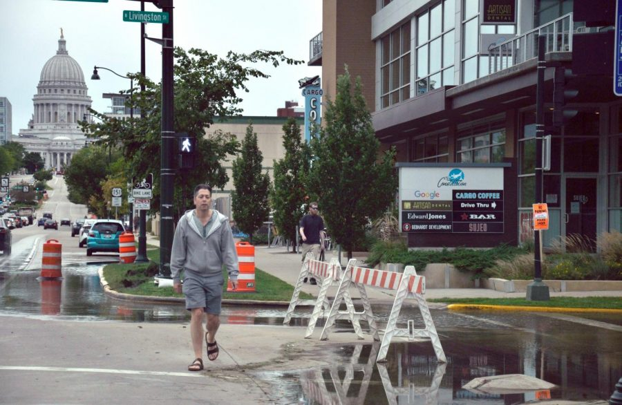 A pedestrian makes his way around the barricades protecting a flooded Livingston Street in downtown Madison on Sept. 7.