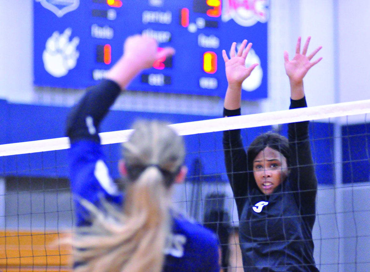 Madison College volleyball player Tianna Sackett reaches up to block an opponents kill during her team's match against Harper College on Sept. 20.