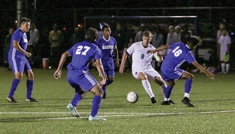 Madison College forward Shane Paterson fights off a trio of Harper College defenders