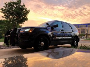 The sun rise brightens the skies behind a Madison College Public Safety patrol car during a recent morning.