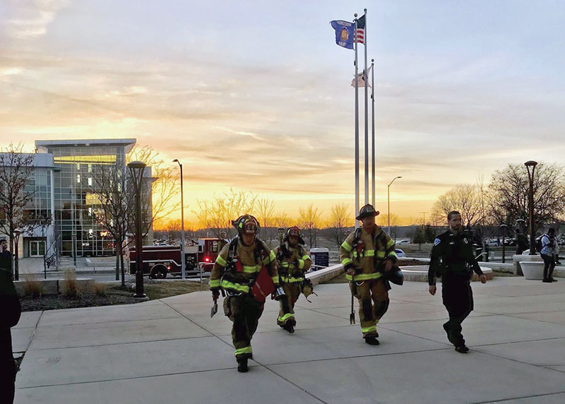 A Public Safety officer leads firefighters into the Truax building during a recent call.