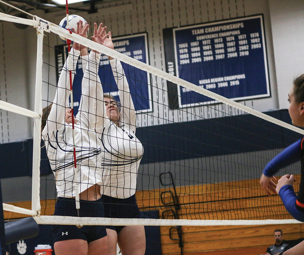 Two Madison College volleyball players attempt to block an opponents shot during a recent match at Redsten Gymnasium.