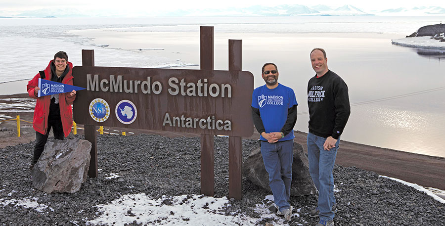 Madison College instructors Andy Kurth, right, and Matthew Lazzara, center, pose for a photograph wearing Madison College shirts at the marking the McMurdo Station in Antarctica.