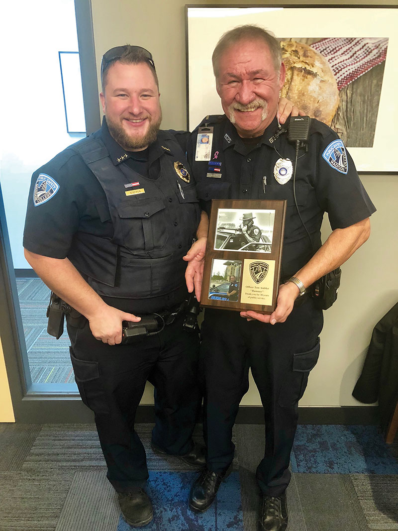 Officer Tom Ambler, right, is presented with a plaque honoring his 38 years of public service. Making the presentation is Sgt. Joe Steffen.