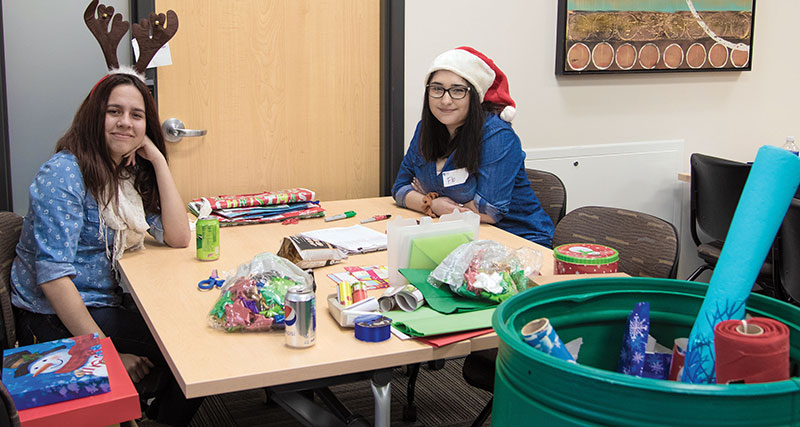 Volunteer Center event coordinator Florencia Balzano, right, and friend Mayra Puyol helped wrap gifts for the Santa's Wish List program on Dec. 1.