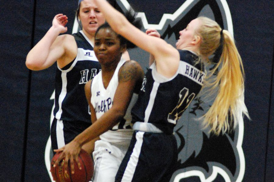 Women's basketball player Shaquita Lee looks to pass the ball after being trapped by two Harper College opponents.