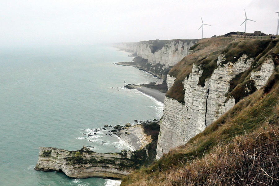 Wind turbines turn atoo a bluff overlooking the sea near Normandy, France