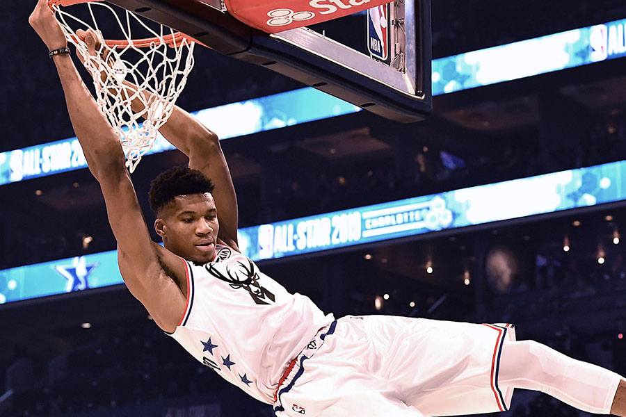 Milwaukee Bucks' Giannis Antetokounmpo swings on the rim after throwing down a two-handed dunk during the NBA All-Star Game at Spectrum Center in Charlotte, N.C. on Sunday, February 17, 2019.